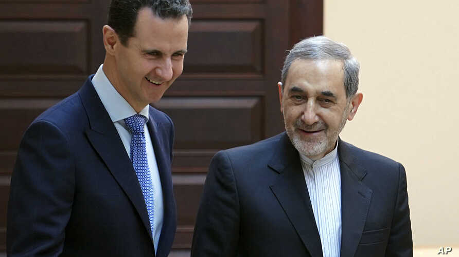 FILE - In this photo released by the Syrian official news agency SANA, Syrian president Bashar Assad, left, meets with Ali Akbar Velayati, an adviser to Iran's Supreme Leader Ayatollah Ali Khamenei, in Damascus, April 12, 2018.
