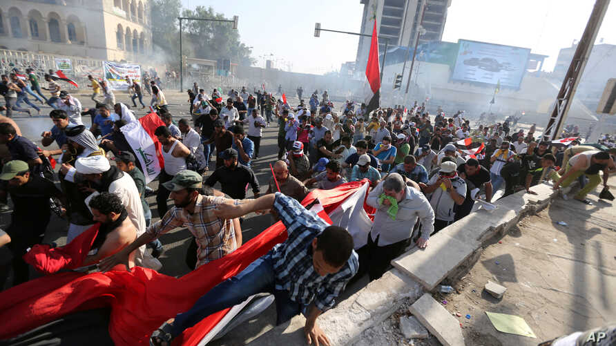 Protesters calling for government reforms run from tear gas fired by Iraqi security forces to disperse the crowd in central Baghdad, Iraq, May 27, 2016.