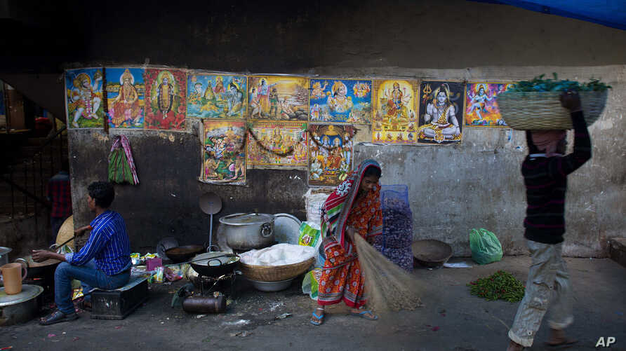 An Indian woman sweeps a pavement past a wall covered with posters of Hindu Gods in Gauhati, India, Monday, Jan. 2, 2017.