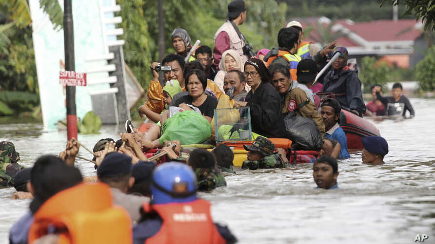 Residents ride a makeshift raft as they evacuate their flooded homes in Makassar, South Sulawesi, Indonesia, Jan. 23, 2019.