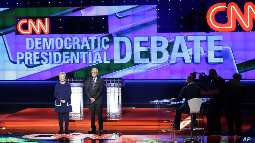 Democratic presidential candidates Hillary Clinton, left, and Sen. Bernie Sanders, I-Vt., take the stage before a Democratic presidential primary debate at the University of Michigan-Flint, Sunday, March 6, 2016, in Flint, Michigan.
