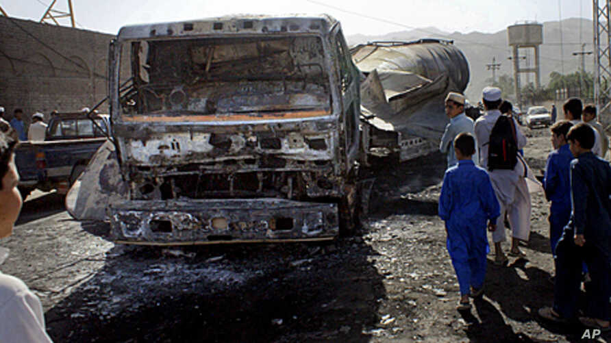 Pakistani youngsters look to a burnt NATO oil tanker caused by alleged militants attacked in Landi Kotal near Afghan border in Pakistan, May 21, 2011