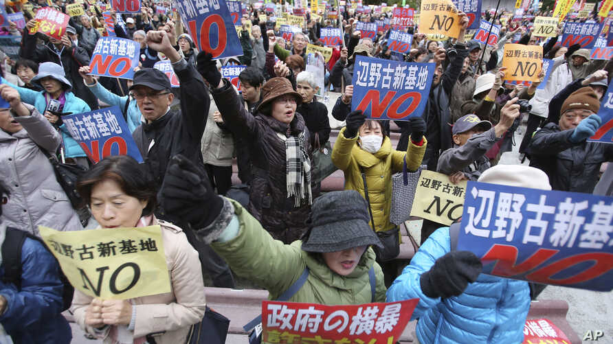 "FILE - Anti-U.S. base protesters hold placards with a slogan that reads: ""No to Henoko new base"" during a rally in Tokyo."