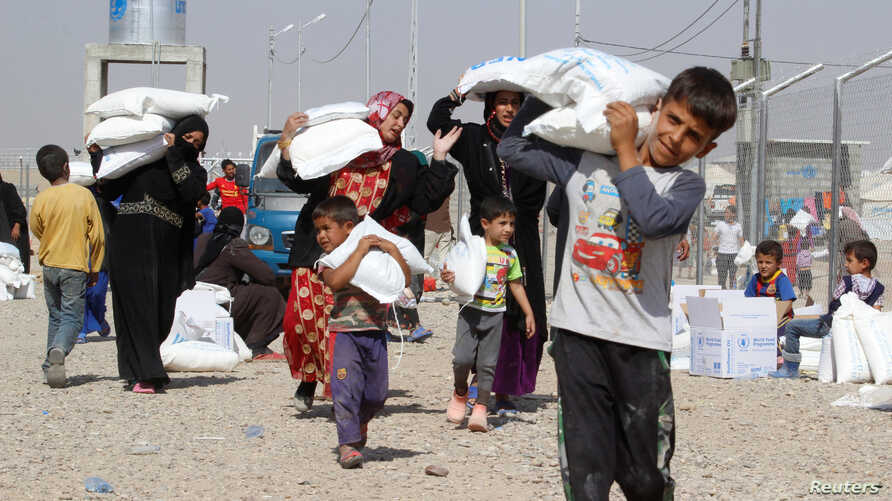 People who fled the Islamic State's strongholds of Hawija and Mosul receive aid at a camp for displaced people in Daquq, Iraq, Oct. 13, 2016.