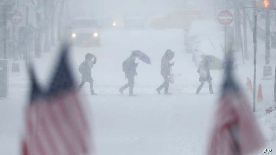 People walk across a snow-covered intersection behind American flags in Hoboken, New Jersey, Feb. 9, 2017.