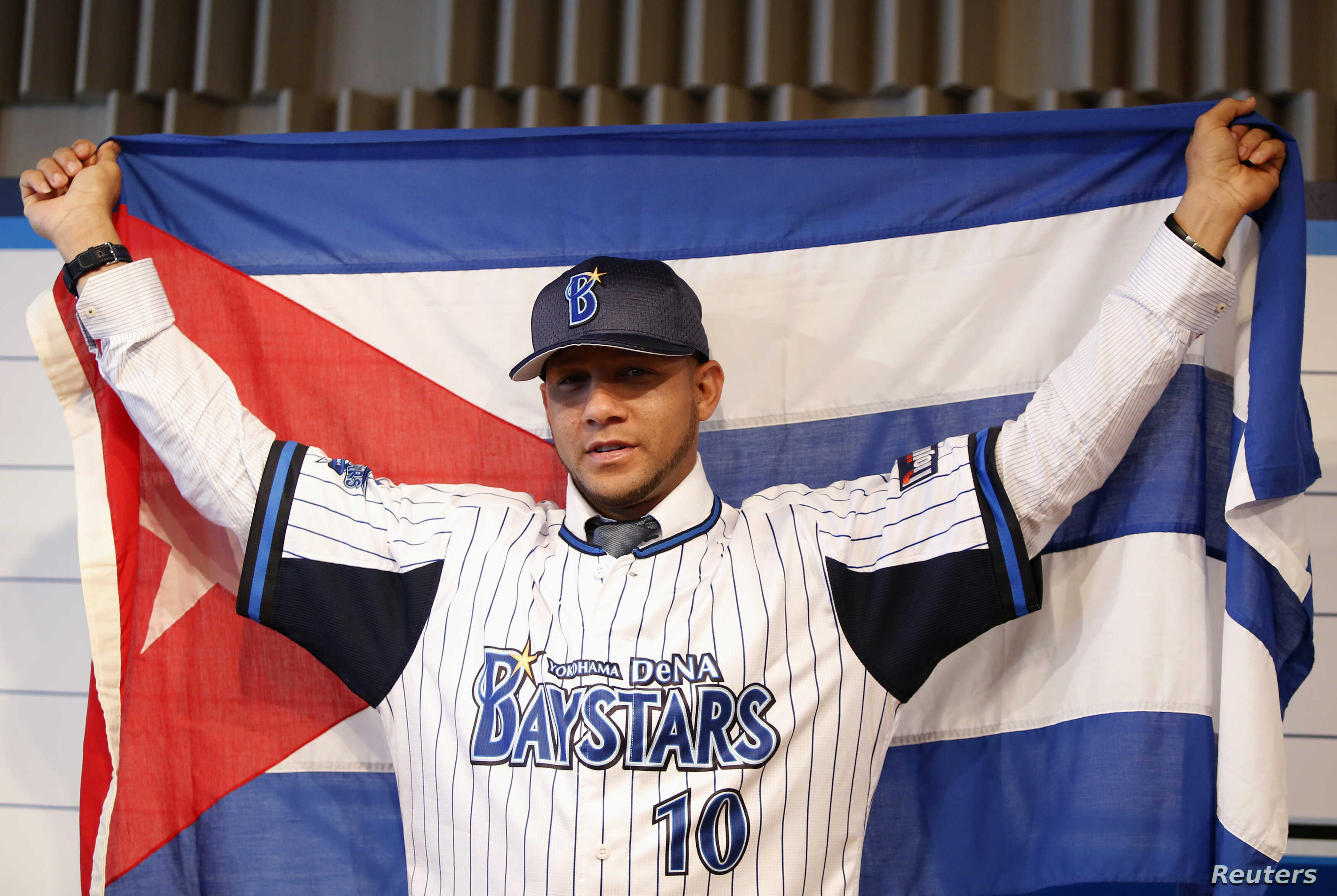 Cuba's baseball player Yulieski Gourriel poses for photographs with the Cuban national flag during a news conference as he joins Japan's Yokohama DeNA BayStars in Yokohama, south of Tokyo, June 2, 2014.
