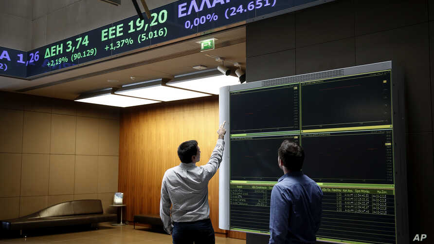 Two men check an index board at the reception hall of the Athens' Stock Exchange, in Athens, Aug. 4, 2015.