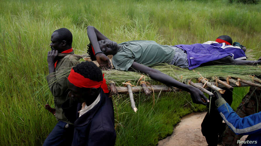 FILE - SPLA-IO (SPLA-in Opposition) rebels carry an injured comrade after an assault on government SPLA (Sudan People's Liberation Army) soldiers, on the road between Kaya and Yondu, South Sudan, Aug. 26, 2017.