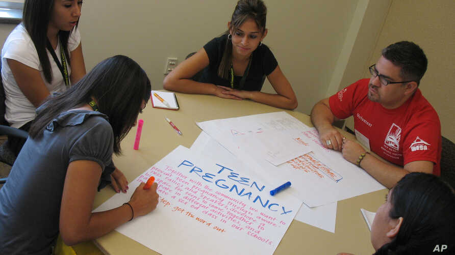 Christopher Ramirez of Albuquerque helps a group of 16 and 17-year-old students from Roswell create a campaign to battle teen pregnancy, Thursday, July 16, 2009 in Albuquerque, N,M,. The teens attended a Hispanic Youth Symposium at the University of