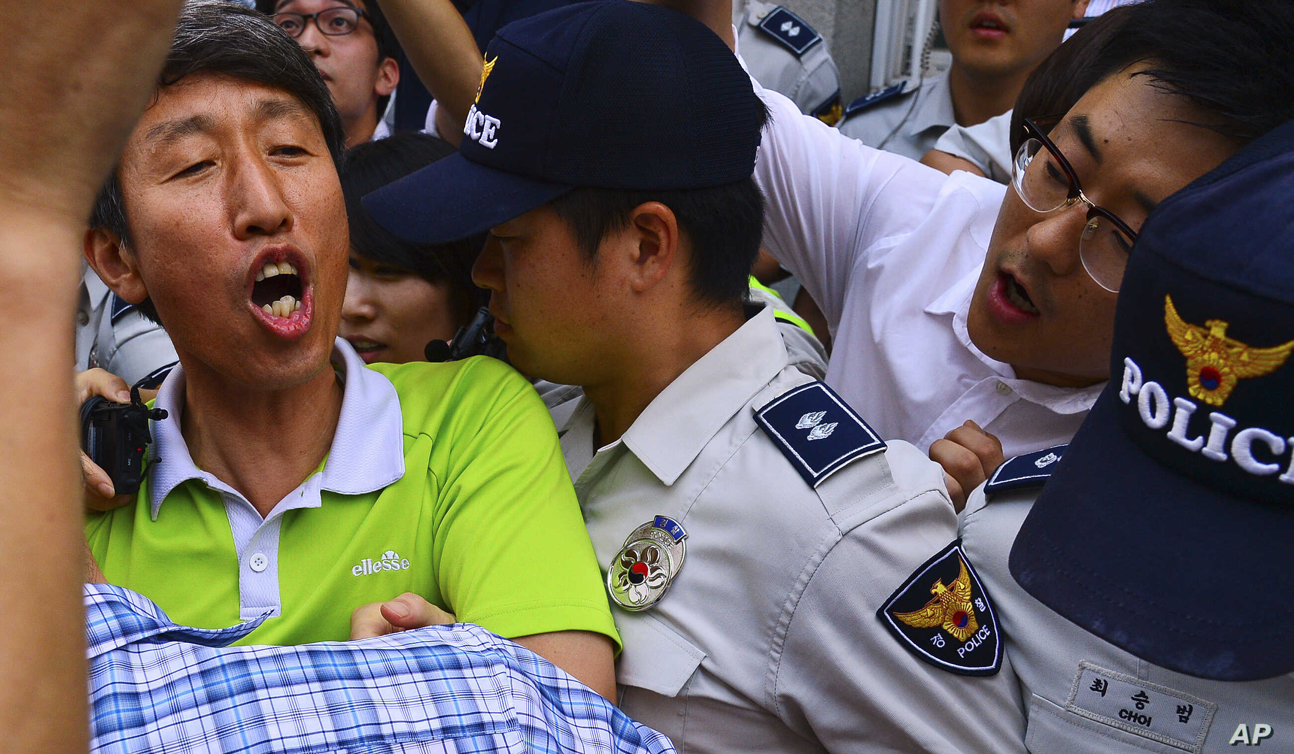 United Progressive Party member Lee Sang-ho, left, is arrested by South Korea's National Intelligence Service at his home in Suwon, south of Seoul, South Korea, Aug. 28, 2013.