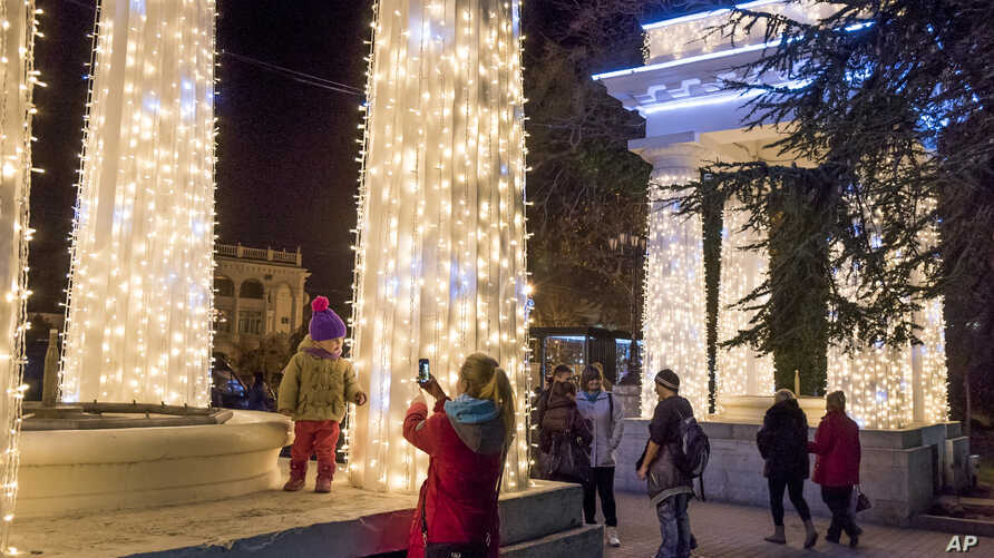 people take pictures at Nakhimov's Square in Sevastopol, Crimea. As New Year's Eve approaches, the central square of Crimea's largest city is festooned with lighted holiday decorations, including a soaring artificial tree that flashes and winks. But