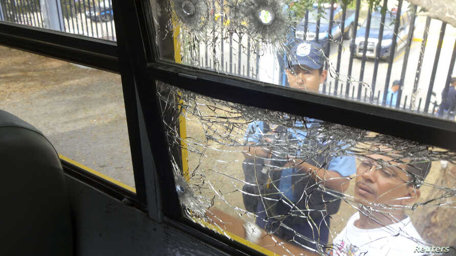 Police officers look at bullet holes in a window that were made during a shooting inside a bus on the Pan-American highway near Ciudad Dario, Nicaragua, July 20, 2014.