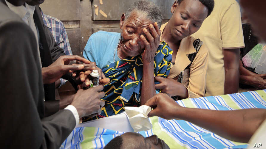 Relatives mourn over the body of Theogene Niyondiko, shot dead Friday by police during a protest against a third term for President Pierre Nkurunziza, in Bujumbura, Burundi, June 9, 2015.