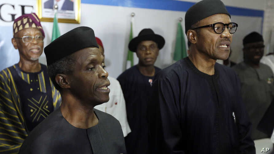 Nigerian former Gen. Muhammadu Buhari, right, along with his deputy, Yemi Osibnajo, sings the national anthem after speaking to journalists in Abuja, Nigeria, April 1, 2015.