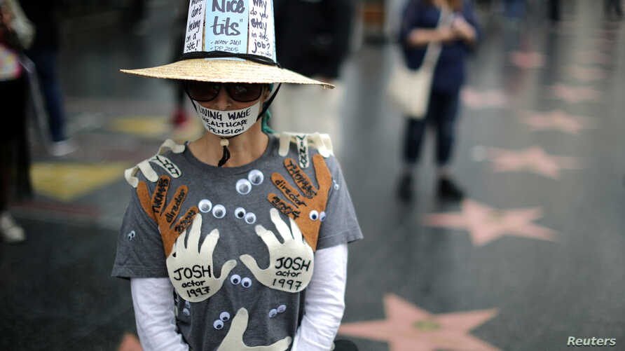 FILE - A woman wearing an outfit with the names of men in Hollywood she claims sexually harassed her, is seen during a protest march for survivors of sexual assault and their supporters, in Hollywood, Los Angeles, California, Nov. 12, 2017.