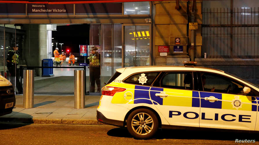 Police officers stand at the end of a tram platform following a stabbing at Victoria Station in Manchester, Britain, January 1, 2019.