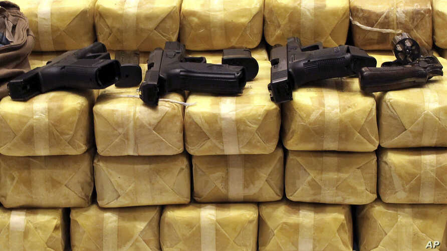 FILE - Guns are displayed on packs of confiscated methamphetamine during a news conference at police headquarters in Bangkok, Thailand, May 21, 2013. Police confiscated nearly 4.5 millions pills of methamphetamine as part of the raid.