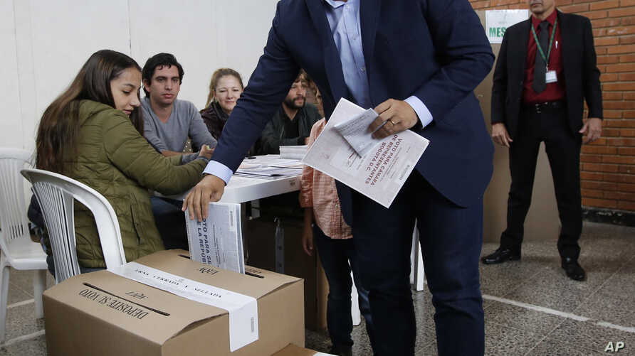 Ivan Duque, presidential candidate with the Democratic Center party, casts his vote during legislative elections in Bogota, Colombia, Sunday, March 11, 2018.