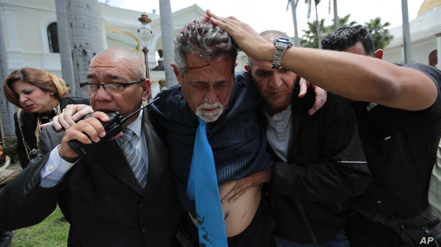 Opposition lawmaker Americo De Grazia is led away by bodyguards and a National Assembly employee after he was injured in a melee with supposed government supporters who tried to force their way into the National Assembly in Caracas, July 5, 2017.