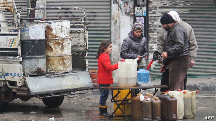 Syrians buy petrol on a street in the northwestern city of Idlib on December 30, 2016. A fragile calm is holding across Syria after a truce brokered by Russia and Turkey came into effect.
