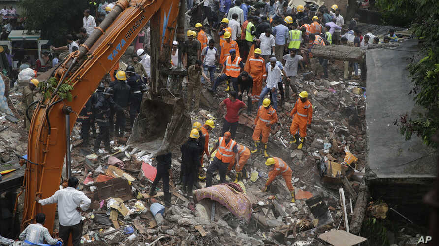 Rescuers sift through debris after a five-story building collapsed in the Ghatkopar area of Mumbai, India, July 25, 2017.