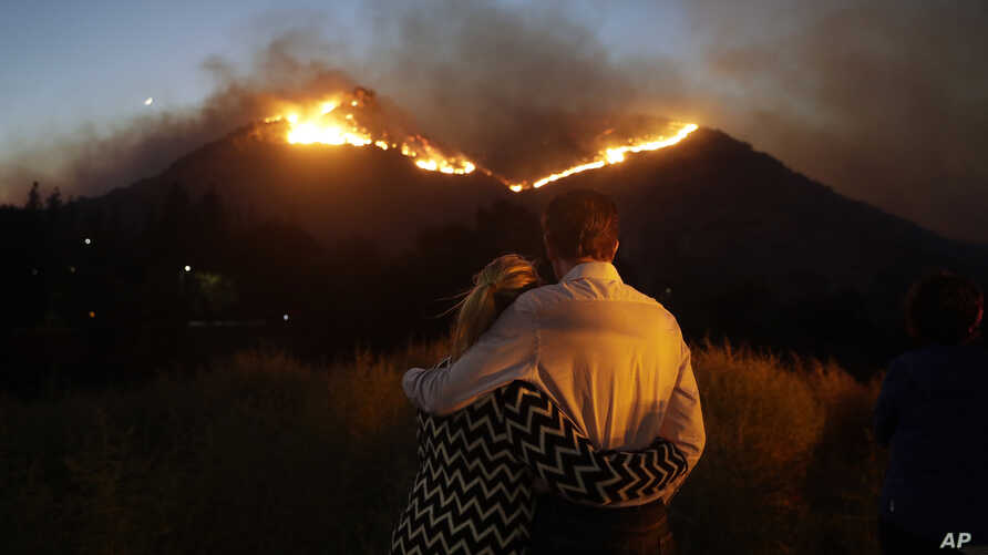 Roger Bloxberg, right, and his wife, Anne, hug as they watch a wildfire on a hill top near their home, Nov. 9, 2018, in West Hills, Calif.