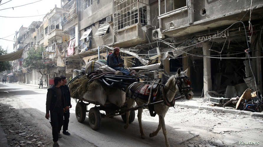 People are seen with their belongings in the besieged town of Douma, Eastern Ghouta, in Damascus, Syria, March 8, 2018.