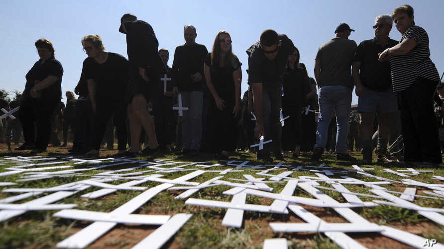 FILE - People place white crosses, symbolically representing farmers killed in the country, at a ceremony at the Vorrtrekker Monument in Pretoria, South Africa, Oct. 30, 2017. U.S. President Donald Trump has tweeted that he has asked the Secretary of