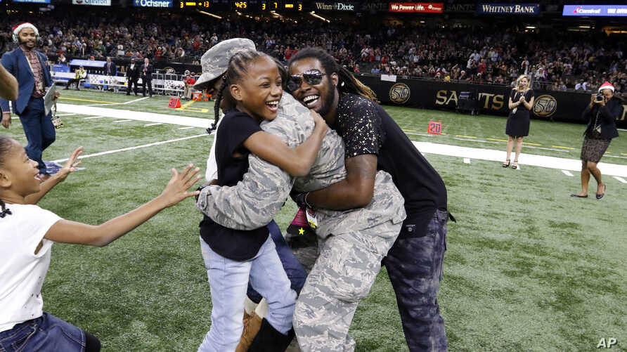 """FILE - Family members rush to greet Air Force Technical Sergeant Anthony Williams, who was based in Qatar, during a surprise reunion at halftime of a National Football League game in New Orleans, Dec. 24, 2016.  Most people would characterize """"blood"""