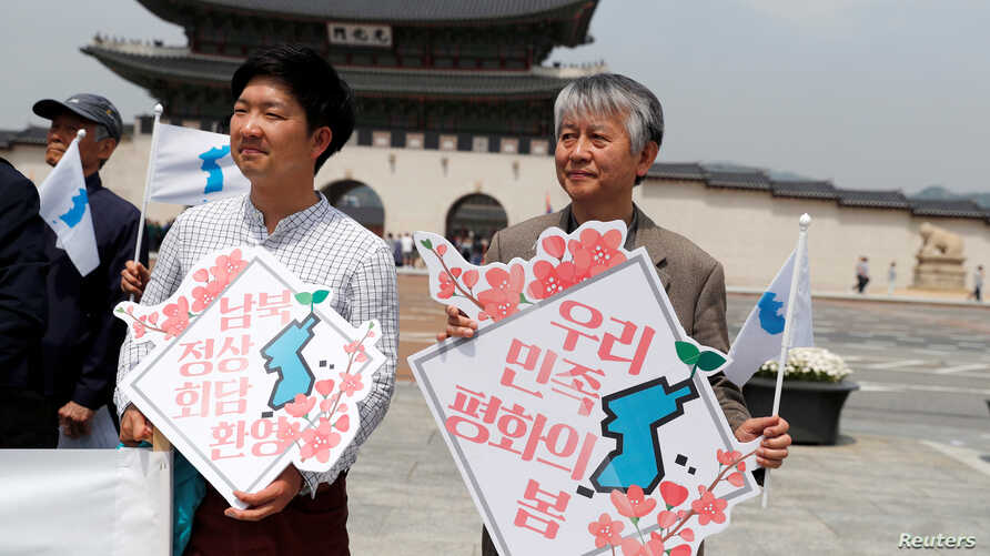 """People hold Korean Unification Flags during a pro-unification rally ahead of the upcoming summit between North and South Korea in Seoul, Apr. 26, 2018. The signs read, """"Welcome inter-Korean summit"""" (L) and """"Peaceful spring for our people"""" (R)."""