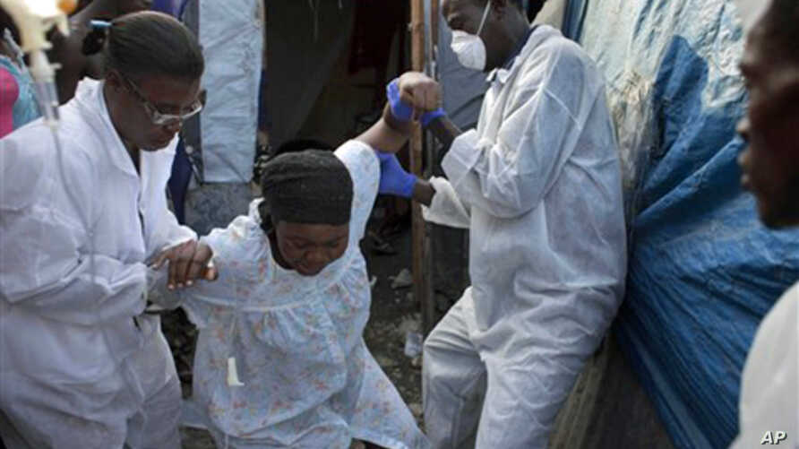 A woman suffering from cholera symptoms is helped at an earthquake refugee camp in Port-au-Prince, Haiti, January 8, 2011