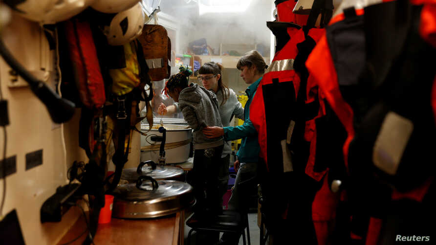 A migrant child helps crew members prepare a meal on the migrant search and rescue ship Sea-Watch 3, operated by German NGO Sea-Watch, off the coast of Malta in the central Mediterranean Sea, Jan. 3, 2019.