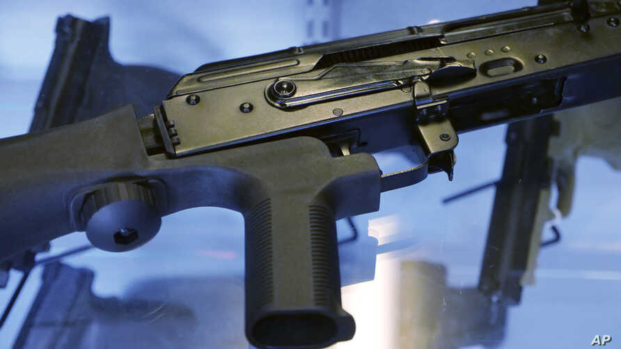 "FILE - A little-known device called a ""bump stock"" is attached to a semi-automatic rifle at the Gun Vault store and shooting range, in South Jordan, Utah, Oct. 4, 2017. The device was used by Las Vegas shooter Stephen Paddock."