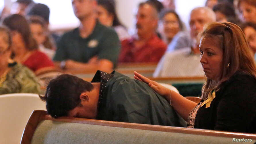 A graduating senior from Santa Fe High School reacts to Friday's school shooting during prayer services at the Arcadia First Baptist Church in Santa Fe, Texas, May 20, 2018.