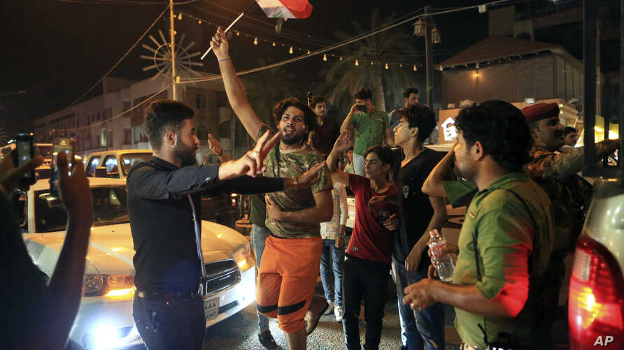 Iraqi security and civilians celebrate while holding national flags, in Basra, 340 miles southeast of Baghdad, Iraq, July 10, 2017. Iraqi Prime Minister Haider al-Abadi declared victory against the Islamic State group in Mosul Monday.