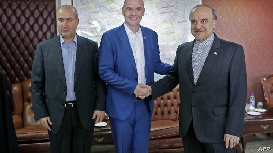 Iran's Minister of Sport and Youth Masoud Soltanifar, right, shakes hands with FIFA President Gianni Infantino during his visit to Tehran, March 1, 2018, accompanied by Iranian Football Federation President Mehdi Taj.