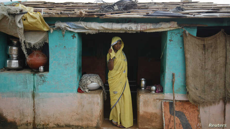 Child bride Krishna, 12, stands at a doorway into her compound in a village near Baran, in India's Rajasthan state, July 30 , 2011.  Despite a law banning girls from marrying before they turn 18, the practice is deeply rooted in tradition and widely ...