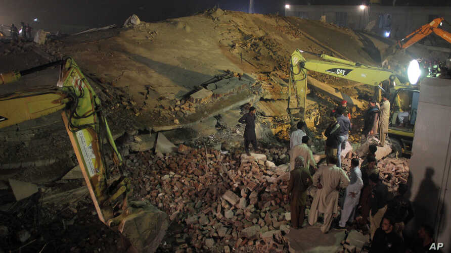 Pakistan rescue workers use heavy machinery to remove debris of a collapsed building in Lahore, Pakistan, Wednesday, Nov. 4, 2015.