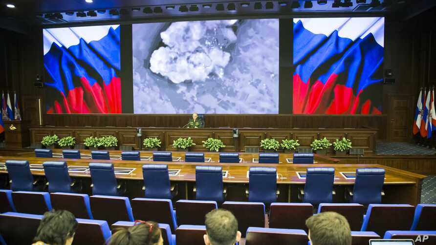 Lieutenant General Sergei Rudskoi of the Russian Military General Staff (background center), speaks to the media in Moscow, March 18, 2016. The screen shows an aerial image of an airstrike during the attack of Russian warplanes in Syria.