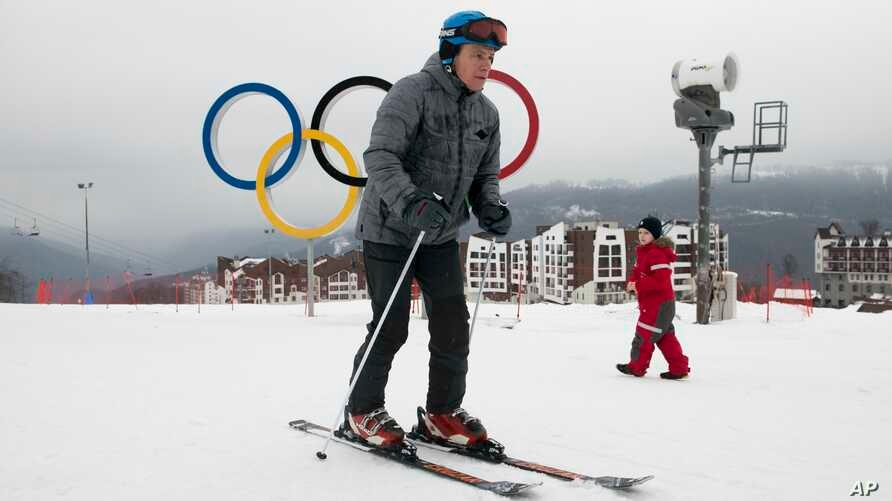 A visitor skis in front of the Olympic rings at the Rosa Khutor ski resort in Sochi, Russia, Jan. 12, 2018.