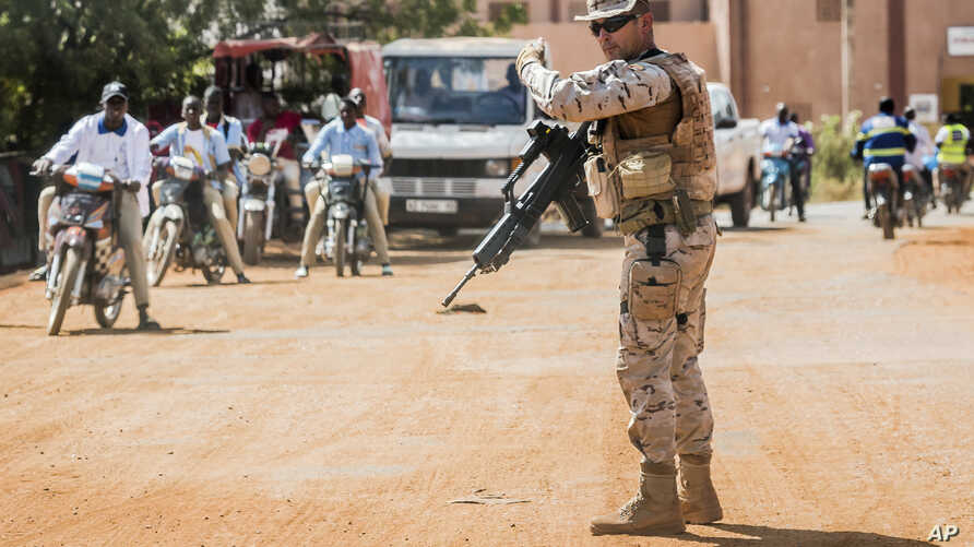 FILE - A soldier from Spain guards the European Union Training Mission (EUTM) camp in Koulikoro, Mali,  Nov. 28, 2017.