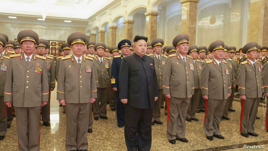 North Korean leader Kim Jong Un, center, pays his respects to his grandfather and North Korea founder, Kim Il Sung, and his father, Kim Jong Il, at Kumsusan Palace of the Sun, Jan. 1, 2015.