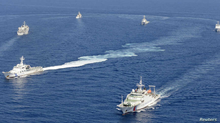 Vessels from the China Maritime Surveillance and the Japan Coast Guard are seen near disputed islands, called Senkaku in Japan and Diaoyu in China, in the East China Sea, in this photo taken by Kyodo September 10, 2013.