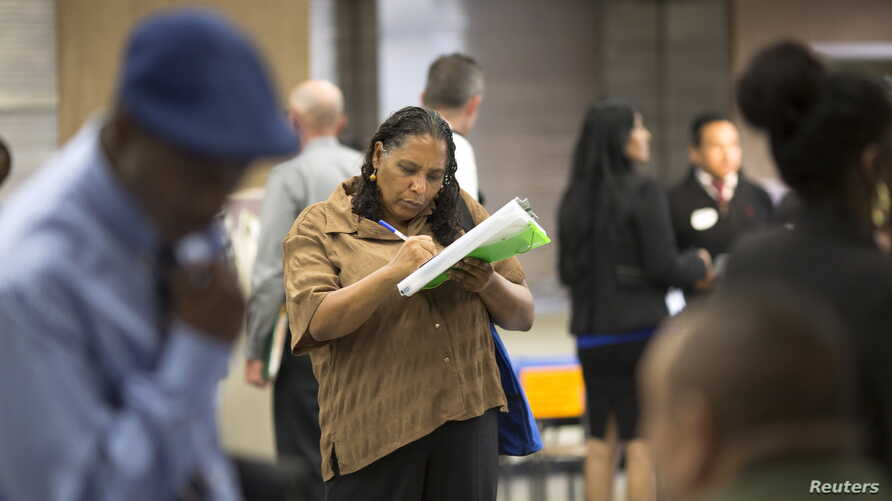 FILE - Malana Long fills out a job application during a job fair for the homeless at the Los Angeles Mission in the Skid Row area of Los Angeles, California, June 4, 2015. The number of Americans filing new claims for unemployment benefits fell more