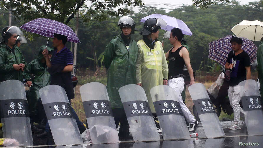 Riot police stand by the side of the road at the entrance of Yuhang town after a night of riots, west of Hangzhou, Zhejiang province, May 11, 2014.