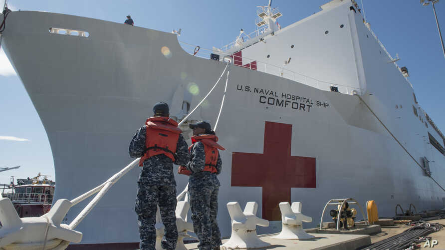 Boatswain's Mate 3rd Class Taryn Armington and Sonar Technician (Surface) Seaman Darian Joseph prepare to cast off mooring lines for the Military Sealift Command hospital ship USNS Comfort.
