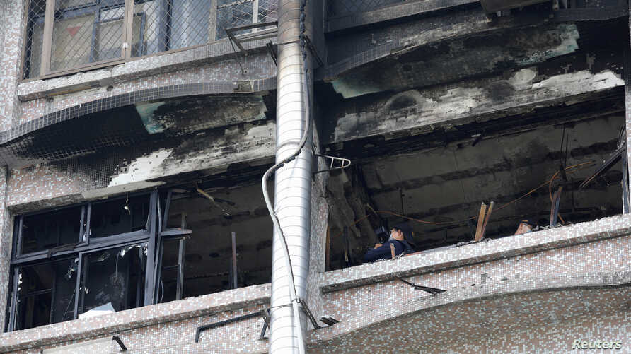 Fire inspectors view damage after a fire broke out at the Taipei Hospital, causing multiple deaths, in New Taipei City, Taiwan August 13, 2018.