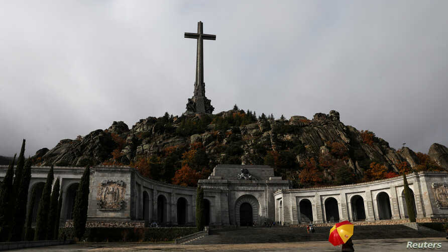 A woman holds an umbrella at the Valle de los Caidos (The Valley of the Fallen), the mausoleum holding the remains of former Spanish dictator Francisco Franco, on the 43rd anniversary of his death in San Lorenzo de El Escorial, outside Madrid, Spain,