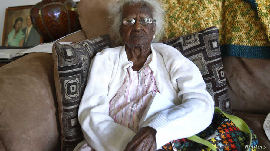 FILE - Jeralean Talley sits on her couch for a photograph during her 115th birthday in her home in Inkster, Michigan, May 23, 2014.