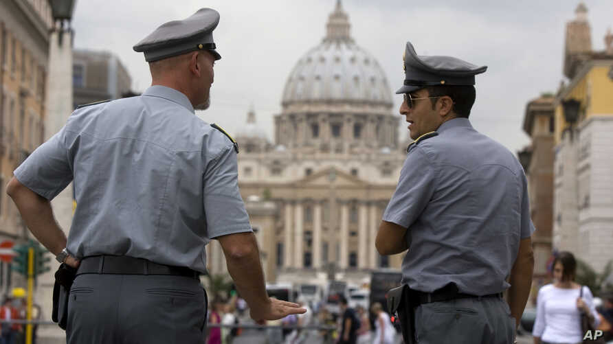 Italian financial police officers talk to each other in front of St. Peter's square at the Vatican, September 2010.